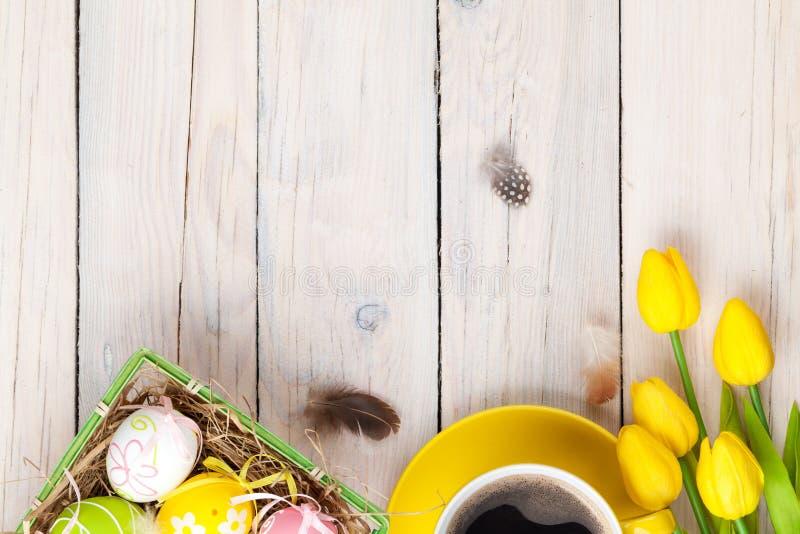 Предпосылка пасхи с красочными яичками и желтыми тюльпанами стоковое изображение rf