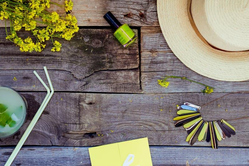 Предпосылка перемещения и каникул - желтый конверт, стекло лимонада, соломенная шляпа, букет wildflowers, маникюр и ожерелье даль стоковые изображения