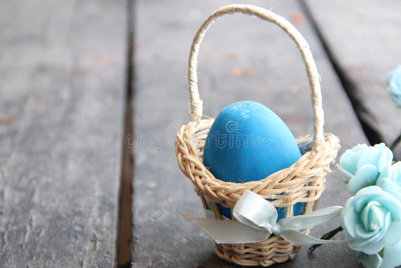 предпосылка покрасила вектор тюльпана формы пасхальныхя eps8 красный Голубое яичко в корзине на деревенской таблице стоковые изображения rf
