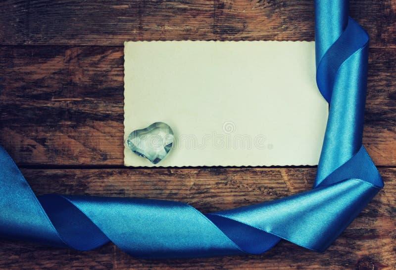 Предпосылка праздника дня валентинки, стеклянное сердце, голубая лента стоковое фото