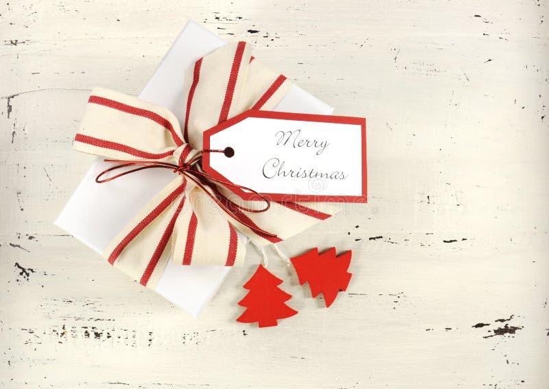 Предпосылка праздника рождества с подарочной коробкой красной и белой темы белой с естественной лентой нашивки холста стоковое фото