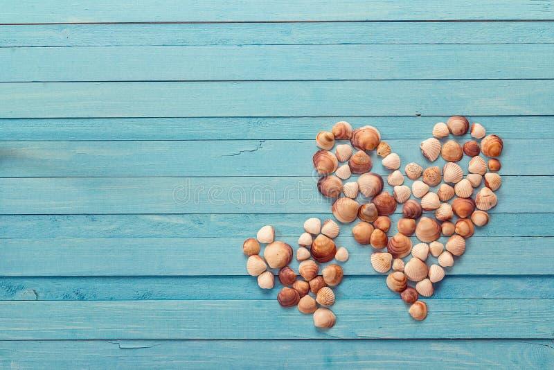 Предпосылка при 2 сердца сделанного seashells на покрашенной сини сватает стоковые фотографии rf