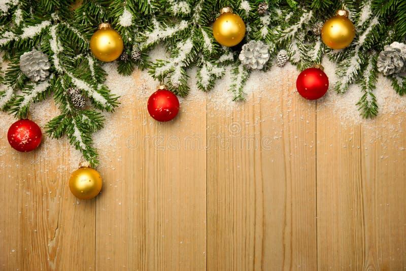 Предпосылка рождества с елью и безделушками на древесине с снегом стоковые фото
