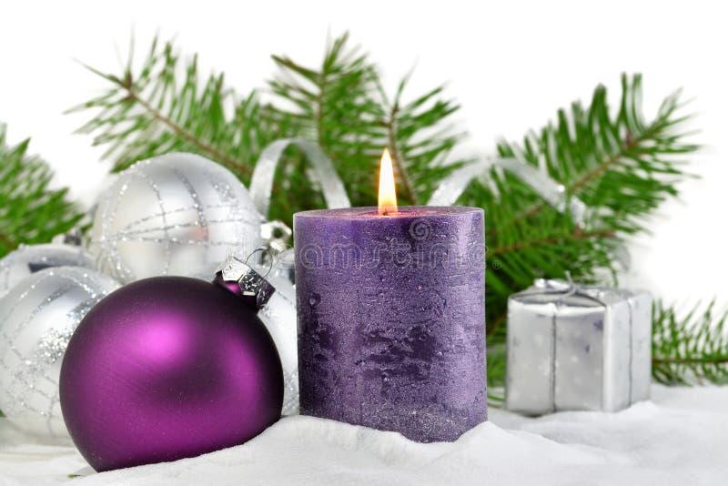 Предпосылка рождества с свечой и украшениями Фиолетовые и серебряные шарики рождества над ветвями ели в снеге стоковые изображения