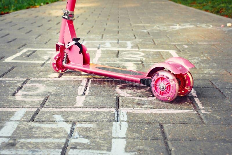 Предпосылка спортивной площадки с розовыми самокатом и hopsco маленького ребенка стоковые фото