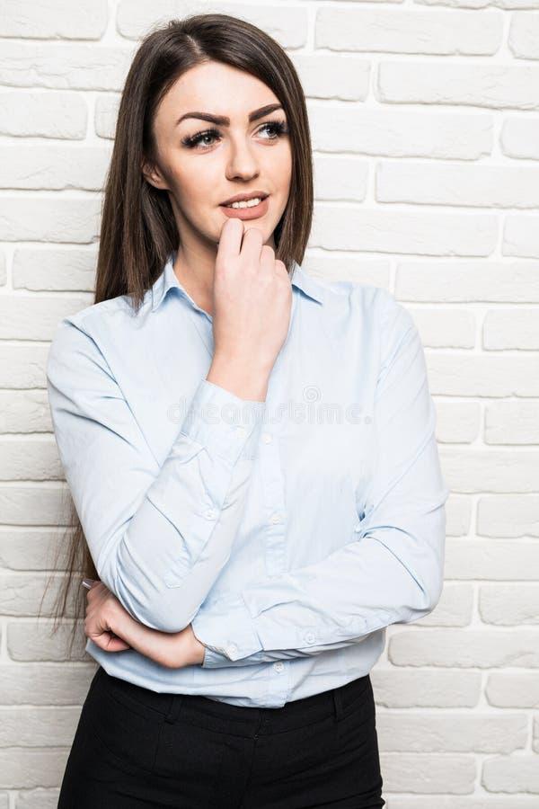 Предпосылка стены кирпичей бизнес-леди daydreaming думая усмехаясь изолированная белая стоковые фото
