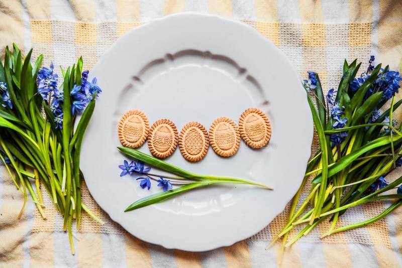 Предпосылка с печеньями серая плита в форме пасхальных яя в голубых snowdrops на checkered полотенце кухни стоковая фотография rf