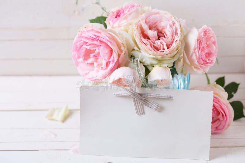 Предпосылка с сладостными розовыми розами цветет в голубой вазе и опорожняет стоковое фото