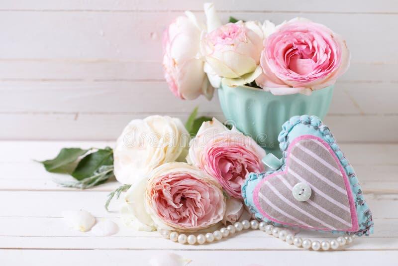 Предпосылка с сладостными розовыми цветками роз и декоративным сердцем стоковая фотография rf