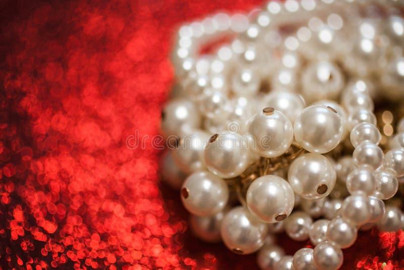 Предпосылка ювелирных изделий с белыми жемчугами на красном ярком блеске стоковое фото