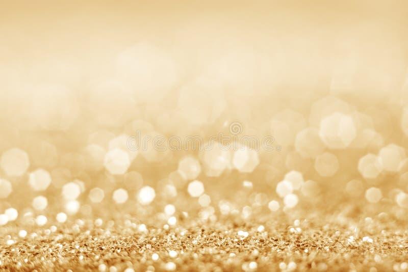Предпосылка яркого блеска золота defocused