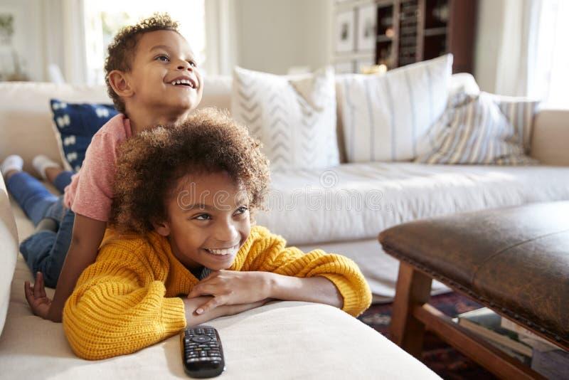 Пре-предназначенная для подростков девушка лежа на софе смотря ТВ в живущей комнате с ее младшим братом сидя на ей назад, близко  стоковые изображения rf