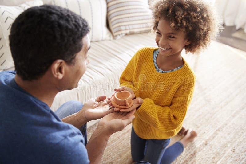 Пре-предназначенная для подростков девушка представляя handmade подарок к ее отцу, повышенному над взглядом плеча, закрывает ввер стоковая фотография