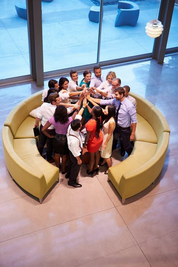 Предприниматели давая один другого высоко 5 в лобби офиса стоковые фото