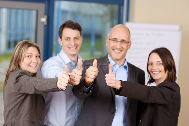 Предприниматели показывая большие пальцы руки вверх подписывают внутри офис стоковое фото