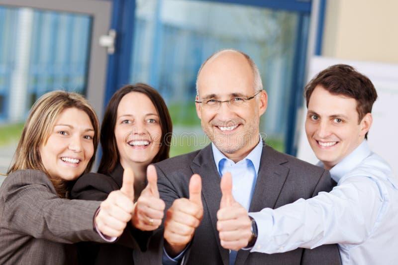 Предприниматели показывая большие пальцы руки поднимают знак стоковая фотография rf