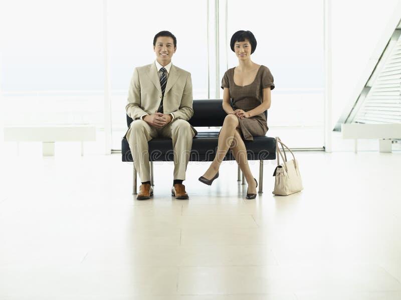 Предприниматели сидя на лобби авиапорта стоковое изображение rf