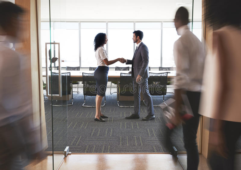 Предприниматели тряся руки в входе к залу заседаний правления стоковые изображения