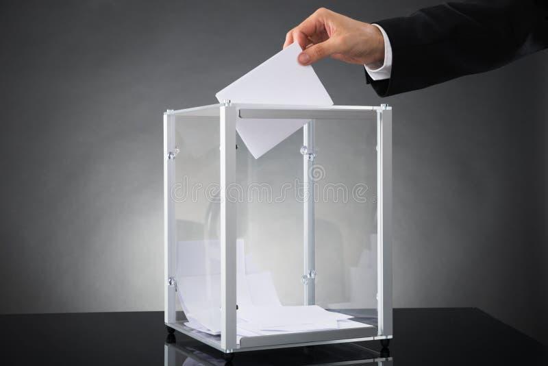 Предприниматель кладя голосование в коробку стоковое фото rf