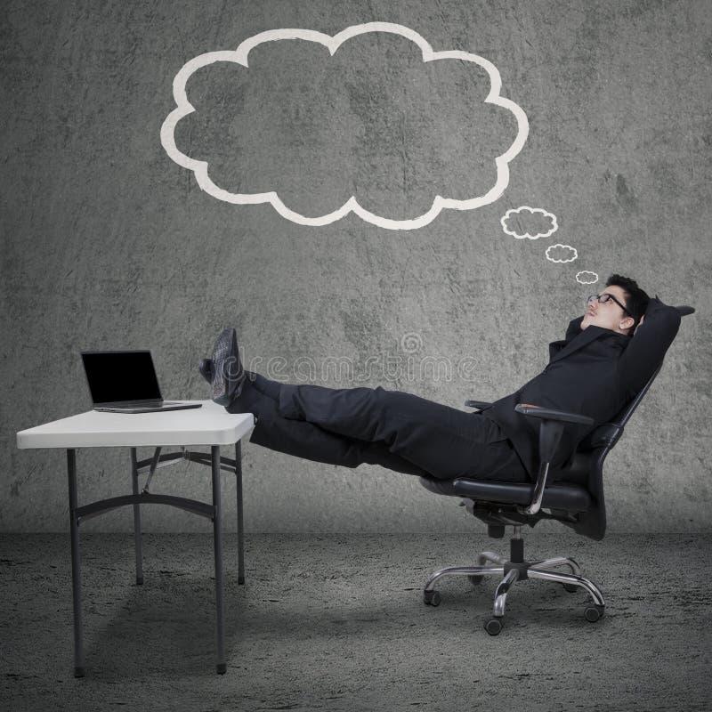 Предприниматель с биркой и мечтать облака стоковое фото