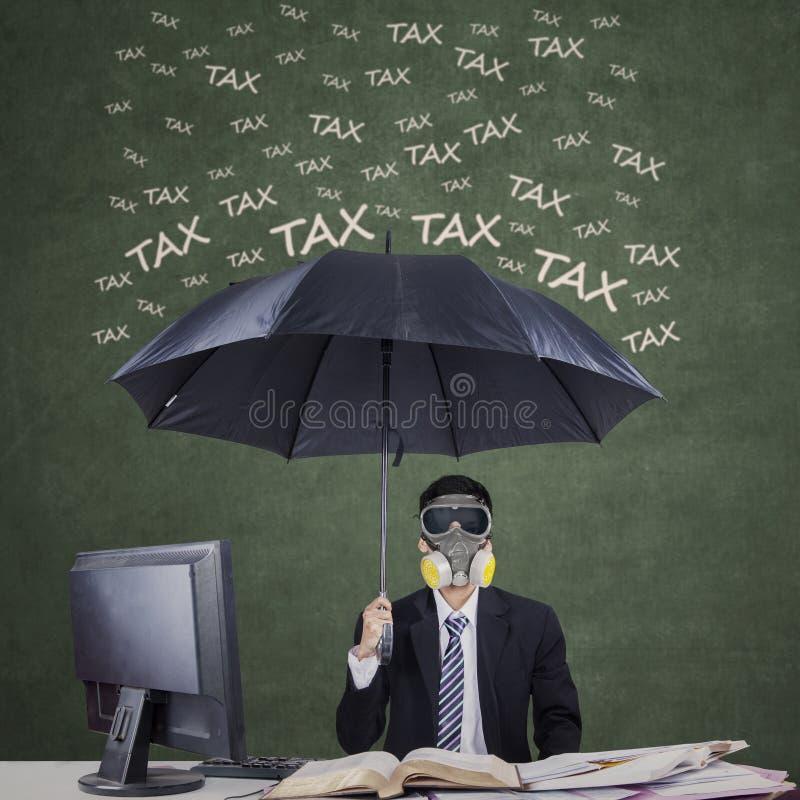 Предприниматель с зонтиком, который нужно защитить от налога стоковая фотография