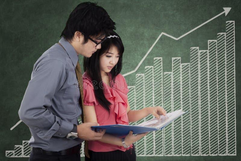 2 предпринимателя обсуждая перед диаграммой стоковое фото