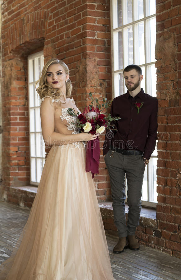 Представление жениха и невеста около окна и кирпичной стены года сбора винограда стоковая фотография
