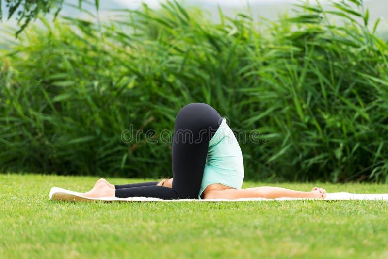 Представление йоги человека Karnapidasana глухое стоковое фото