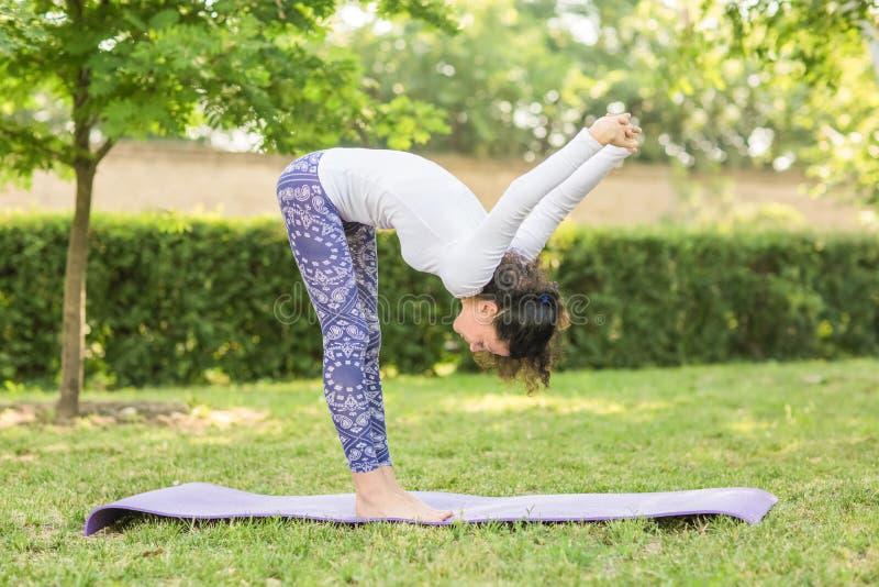 Представление йоги чудесной и милой женщины практикуя в парк с много деревьями Очаровательная дама делает тренировки спорт стоковая фотография rf
