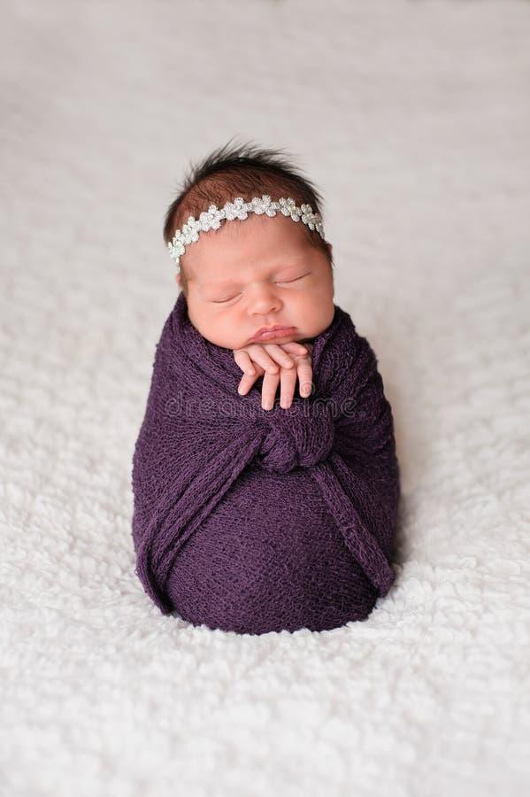 Представленная Newborn девушка спать в пурпуре Swaddle стоковые фото