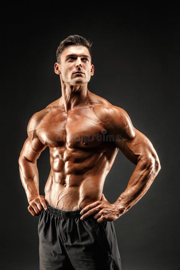 представлять культуриста Человек muscled фитнесом на темной предпосылке стоковая фотография