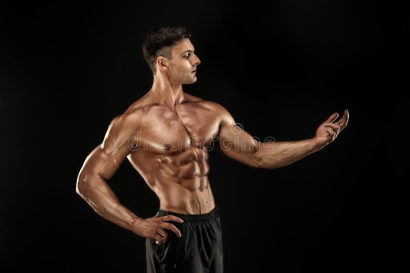 представлять культуриста Человек muscled фитнесом на темной предпосылке стоковое фото