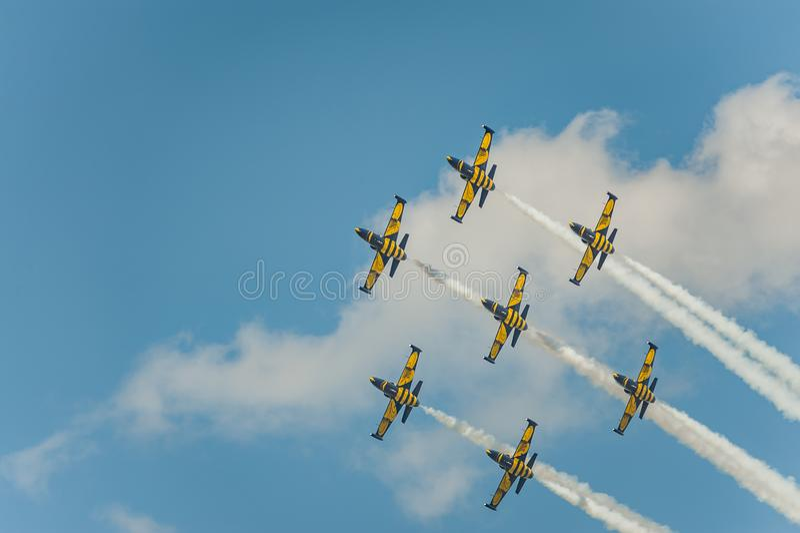 Прибалтийские пчелы объединяются в команду выполняют полет на авиасалоне и листья за a курят в небе стоковые изображения