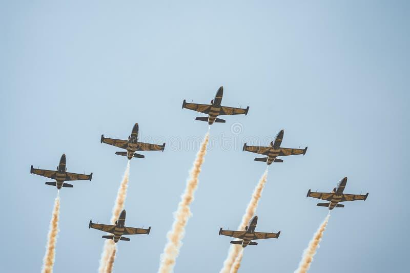 Прибалтийские пчелы объединяются в команду выполняют полет на авиасалоне и листья за a курят в небе стоковая фотография
