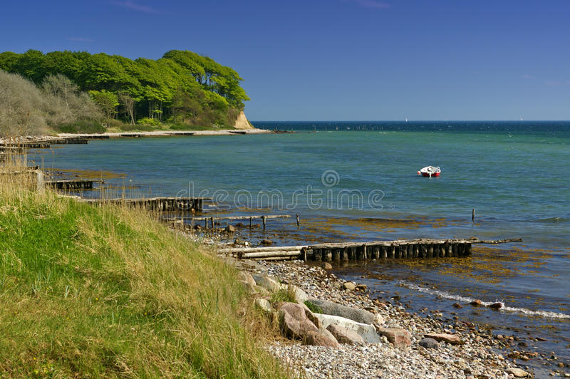 Прибалтийский seashore с пляжем, поставленной на якорь шлюпкой и лесистой скалой стоковое изображение