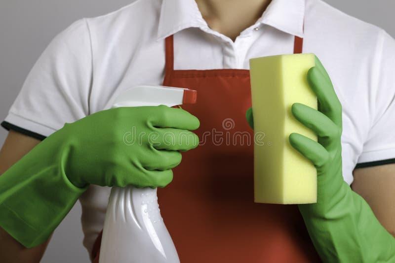 Приближается женщина в фартуке и перчатки держат в руках флакон с брызгами и губку стоковые фотографии rf