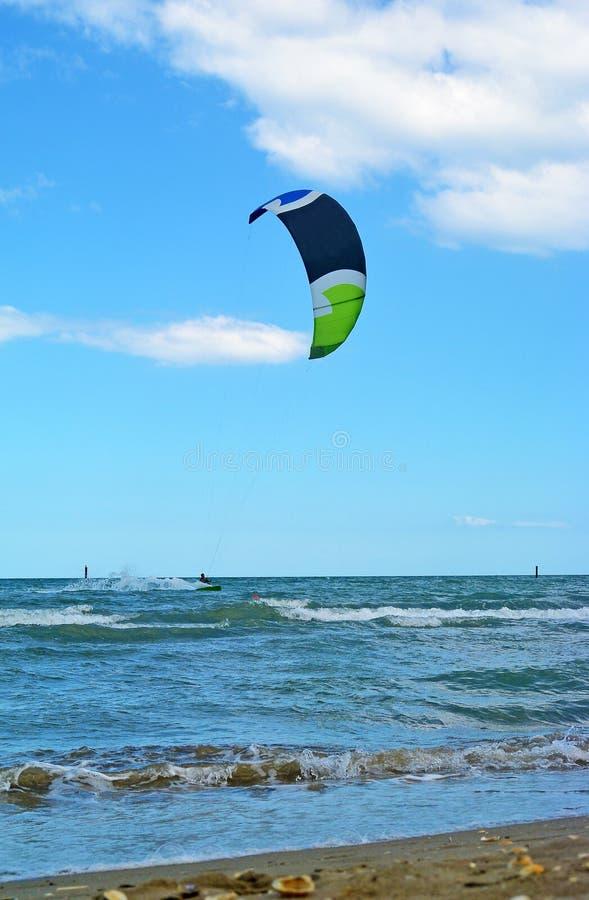 Прибой змея езды молодого человека в море, весьма спорте Kitesurfing или kiteboarding стоковая фотография