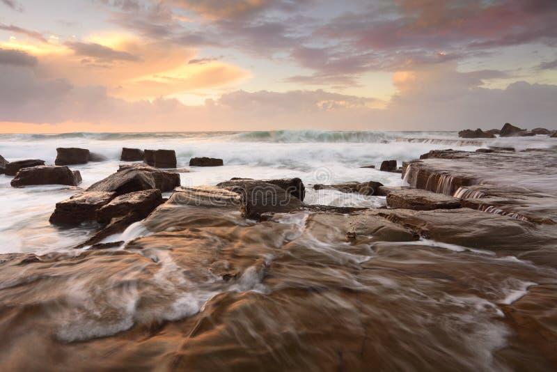 Прибой и переполнения океана на восходе солнца стоковая фотография