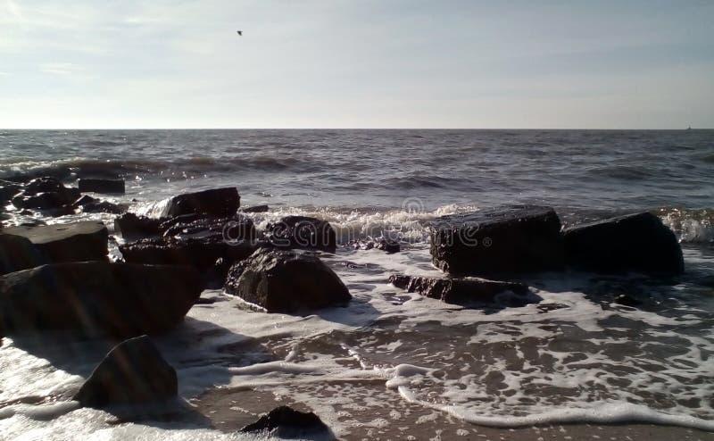 Прибой моря на солнечный день На переднем плане, влажный песок, темные влажные камни, небольшие волны с брызгает и белая пена стоковое изображение