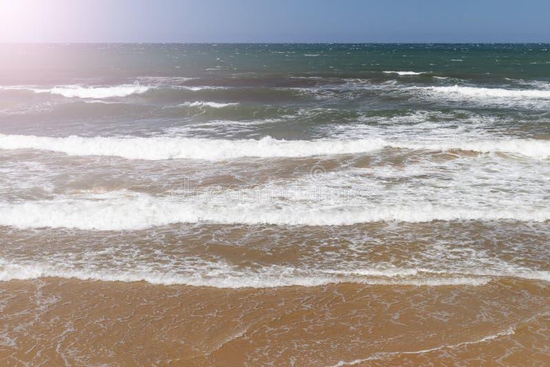 Прибой океана с водой песчаного пляжа и бирюзы на солнечный летний день стоковые изображения rf