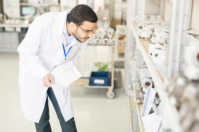 Приборы занятого аравийского инженера рассматривая в складе стоковое изображение