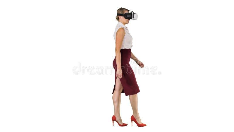 Прибор виртуальной реальности молодой женщины нося и идти на белую предпосылку стоковые фотографии rf