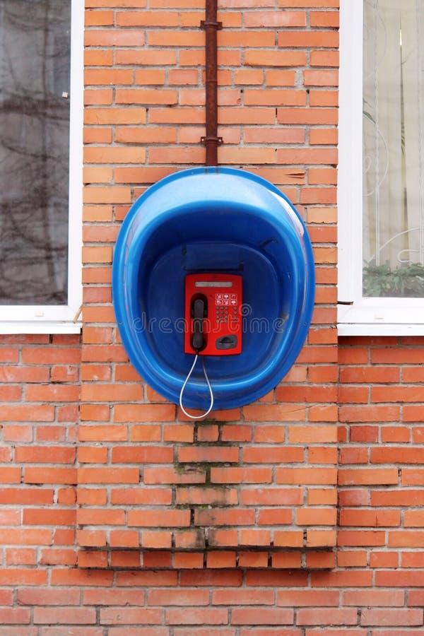 Прибор красного телефона общественный защитил голубую будочку на кирпичной стене дома стоковые фотографии rf
