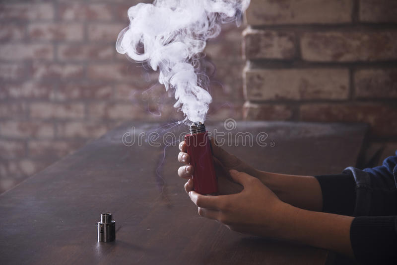 Прибор Vaping внутри в руке ` s женщины стоковое фото