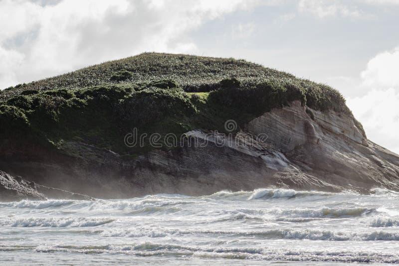 Прибрежная скала противостоит где земля встречает море Пляж Wharariki стоковое фото