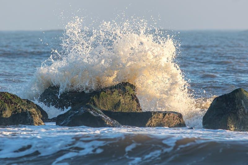 Прибрежная эрозия Волна разбивая против утесов обороны потока моря стоковые изображения