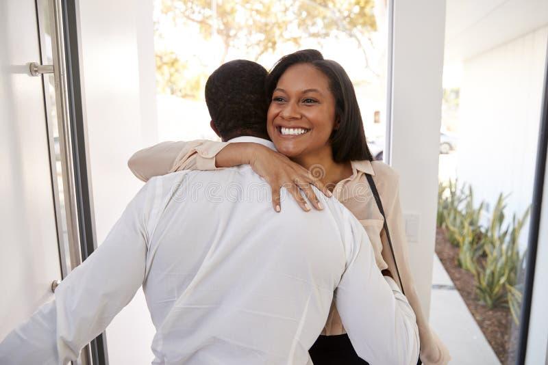Приветствие человека и обнимать жену коммерсантки по мере того как она возвращает дом от работы стоковые фото