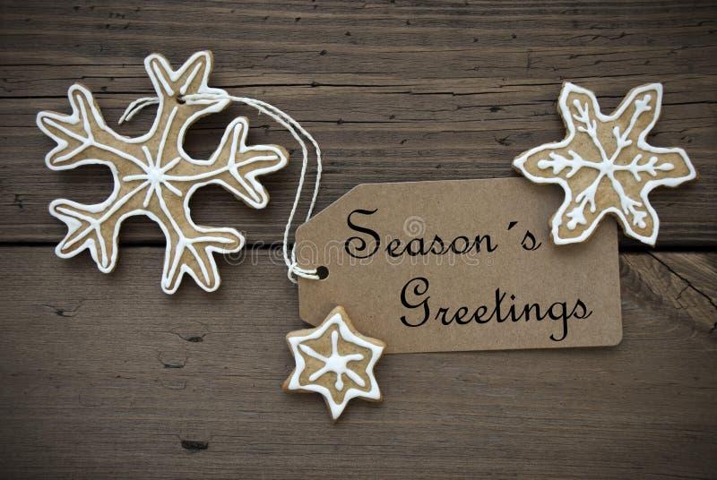 Приветствия сезона на ярлыке с печеньями хлеба имбиря стоковое изображение
