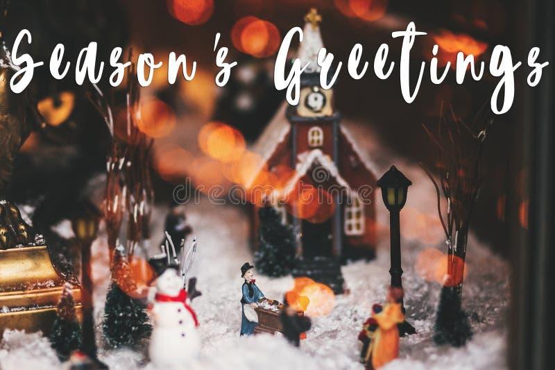 Приветствия сезона отправляют SMS на меньшем городе рождества в миниатюрных wi стоковые фотографии rf