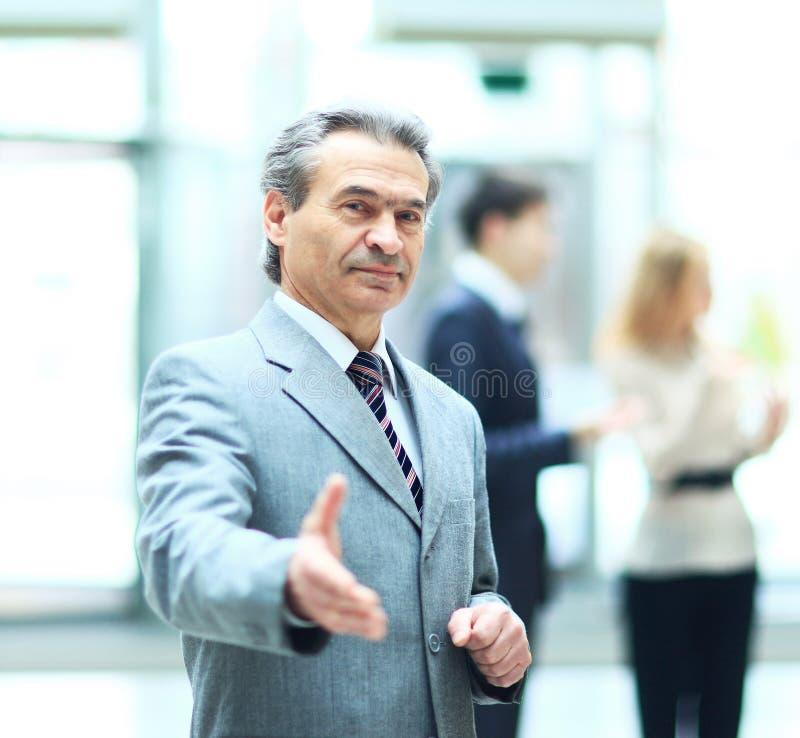 Приветствующий бизнесмен готовый к рукопожатию при расширенная рука, сотрудничает на фоне работы его команда стоковая фотография rf
